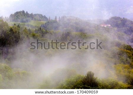 "fog over mountain landscape in the ""styrian tuscany"". southern styria - stock photo"