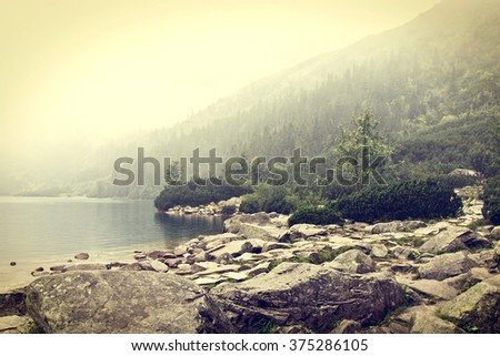 Fog over mountains lake. Nature conceptual image. Morskie Oko in Tatry, Poland. Vintage colors picture. - stock photo