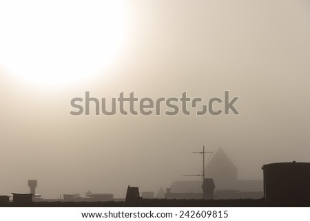 Fog over roof tops in Gothenburg, Sweden on a sunny morning - stock photo