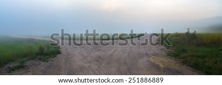 Fog over the old rural gravel road. Panoramic shot. - stock photo
