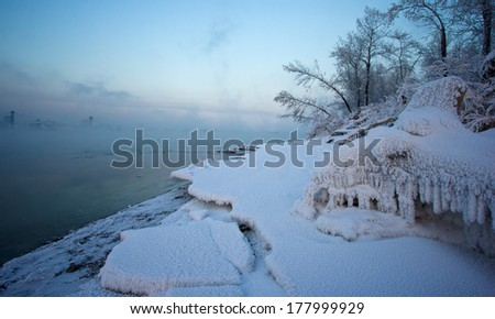 Fog over the river. On the bank of the river grass and trees covered with snow. Fog lights illuminated the setting sun. - stock photo