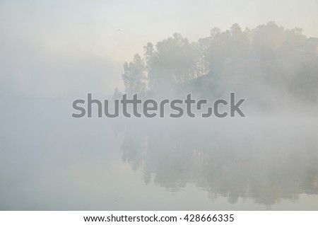 fog over the water . morning fog. thick morning mist over the lake . around the lake grow birch . landscape early in the morning warm . the sun rises and lights up the forest with a pond in the fog .  - stock photo