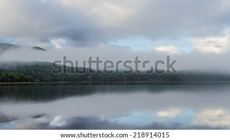 Fog rolls by the side of Loch Morlich, Scotland  - stock photo