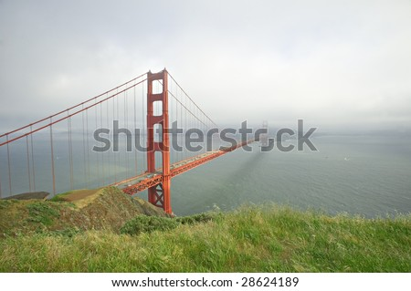 Fog sets over San Francisco with Golden Gate Bridge in foreground - stock photo