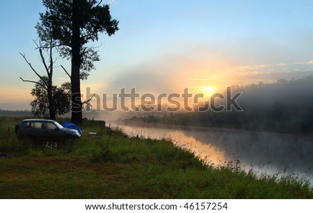 fog sunrise on the river with camping - stock photo