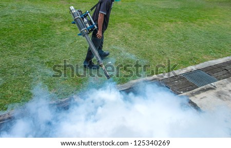 Fogging into the drain to prevent spread of dengue fever - in soft motion blur - stock photo
