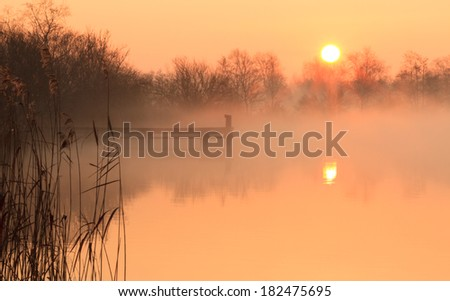 Foggy and yellow sunrise at a jetty. - stock photo