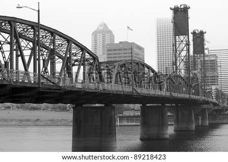 Foggy day with a diminishing view of the Hawthorne Bridge on the Williamette River in Black and White - stock photo
