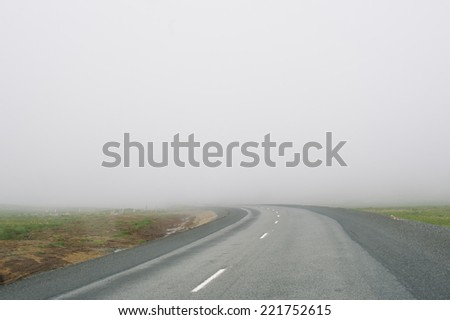 foggy empty driving road - stock photo