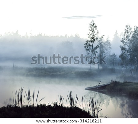 Foggy evening landscape with small lake, trees  and rowboat  - stock photo