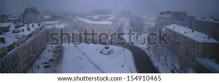 Foggy evening view from the bell tower of St. Sophia Orthodox monastery opens a panorama of snow-covered town, the paths of which are single figures of passers-people  - stock photo