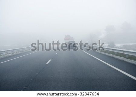 Foggy gray road, cars driving fading into the fog - stock photo