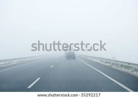 Foggy gray road, cars driving vanish into the fog - stock photo
