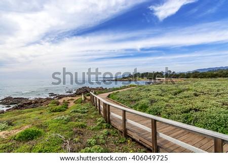 Foggy, hazy, lazy sunlit day on the boardwalk, blue sky & aquamarine sea, waves gently crashing on the shoreline at Moonstone Beach, along Big Sur Coast, California Central Coast, near Cambria CA. - stock photo
