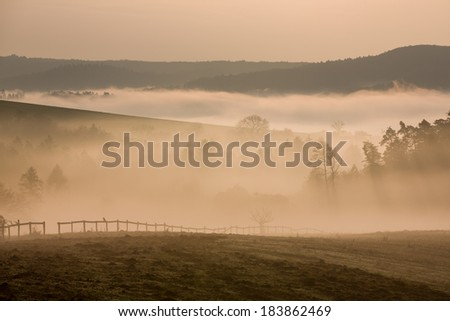 Foggy hills and valleys with fence in autumn dawn - stock photo