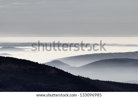 Foggy hills in a winter day - stock photo
