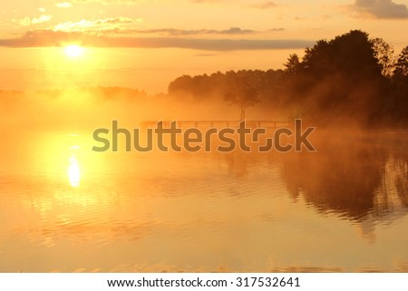foggy lake at sunrise - stock photo