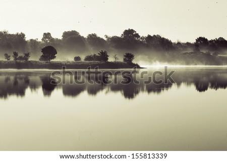 Foggy landscape on the lake - stock photo