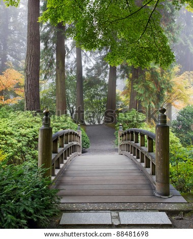 Foggy Morning by Wooden Foot Bridge at Japanese Garden in Autumn - stock photo