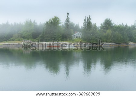 Foggy morning in one of the many coves in Penobscot Bay in Maine. The calm ocean waters provide beautiful reflections of the landscape.