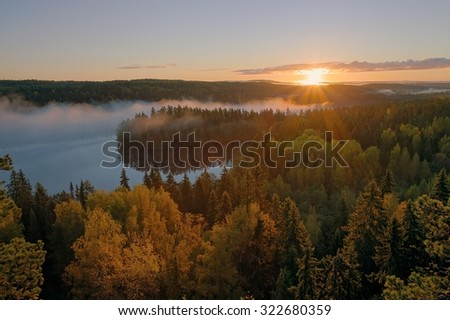 Foggy morning inf the Aulanko nature reserve park in Finland. The sun hits the fog above the lake in the early morning. HDR image. - stock photo