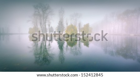 Foggy morning panorama in the autumn park near the lake. Vintage stylization - stock photo