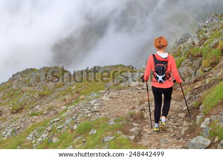 Foggy mountain and woman hiker walking on rocky trail - stock photo