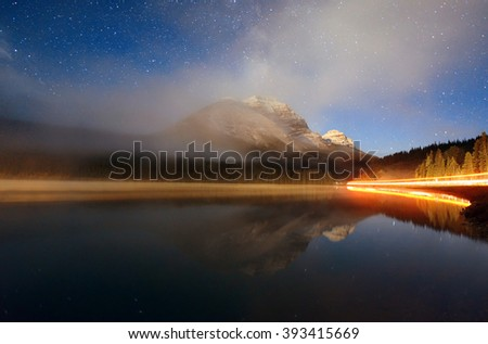 Foggy mountain at night over lake with stars and traffic light trail in Banff National Park, Canada - stock photo