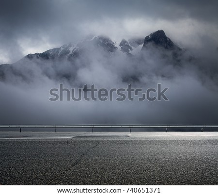 Foggy mountains and asphalt road. Landscape in rainy day