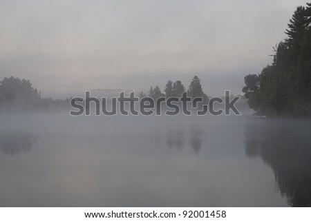 Foggy Muskoka lake at dawn - stock photo