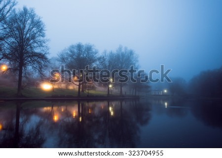 Foggy night scene at pond with lights and gazebo in distance  - stock photo