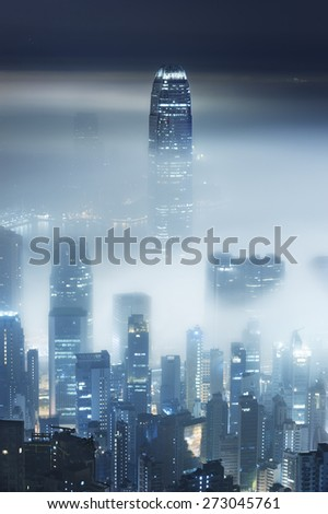 Foggy night view of Victoria harbor in Hong Kong city - stock photo