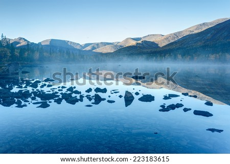 Foggy Polygonal freshwater lake with rocks in the foreground in Hibiny mountains in the early morning before sunrise - stock photo