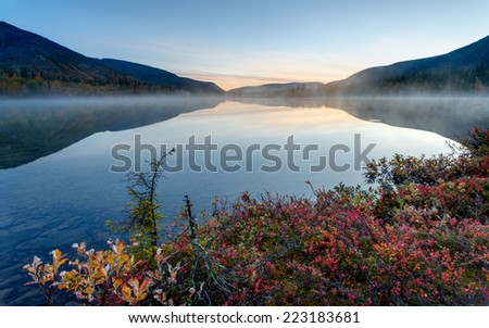 Foggy Polygonal lake with colorful greenery in the foreground in Hibiny mountains in the early morning before sunrise - stock photo