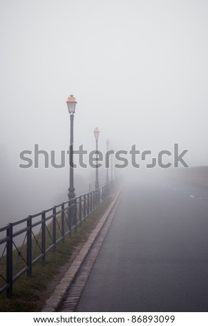 Foggy road with old lamps. France, Saint-Emilion. Toned and vignetted image - stock photo