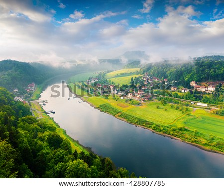 Foggy spring view of Rathen village from viewpoint of Bastei in Saxon Switzerland Germany. Morning in  Sandstone Mountains, Saxony, Germany, Europe. Artistic style post processed photo. - stock photo