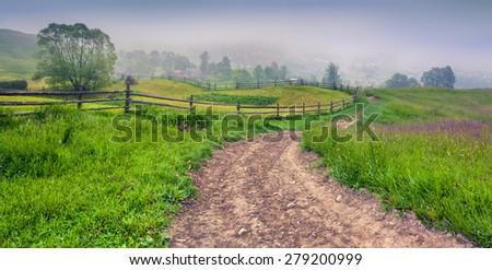 Foggy summer panorama of the mountain village. - stock photo