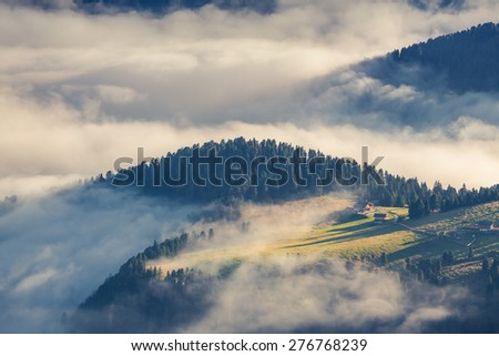 Foggy summer sunrise in the Italian Alps. Ferchetta mountain range, Dolomites mountains, Italy, Europe. - stock photo