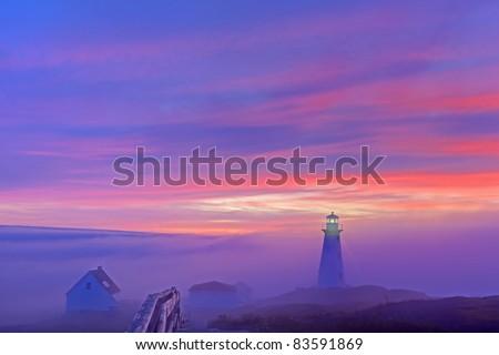 Foggy sunrise at Cape Spear. - stock photo