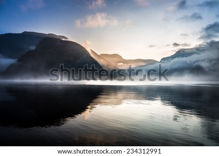 Foggy sunrise over the mountains - stock photo