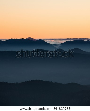Foggy sunset in the mountains. Mist is covering the hills in the early evening.