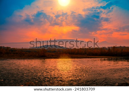 Foggy sunset over mountain river - stock photo