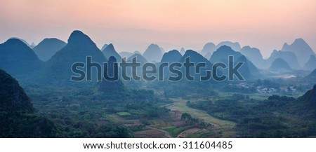 Foggy sunset. The view from the top of the Vine Mountains near Guilin - China (panorama) - stock photo