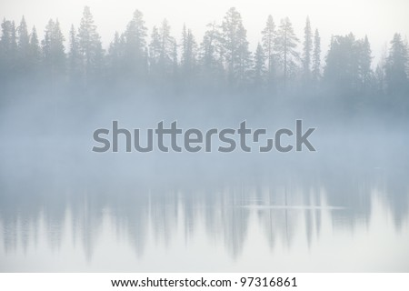 Foggy weather early in the morning on the lake. - stock photo