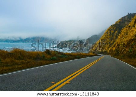 Foggy winding road along California coast - stock photo