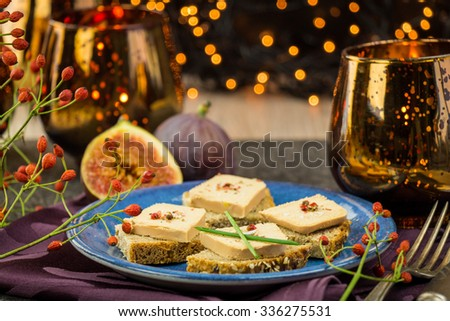 Foie gras on wholewheat bread with juicy ripe figs served as snacks at a festive celebration with colorful party lights in the background - stock photo