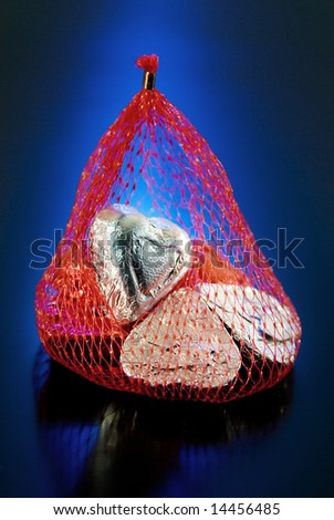 Foil wrapped Valentine hearts in red mesh bag. - stock photo