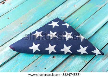 Folded American Flag on Blue Distressed Wood Background - stock photo