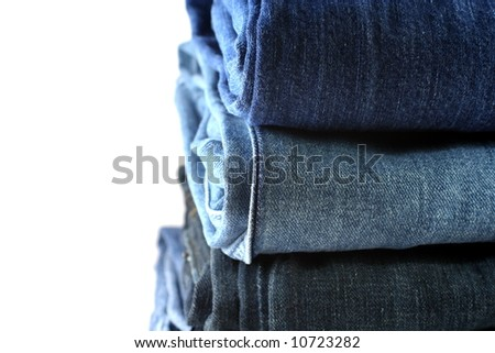 folded and stacked blue jeans on a white background