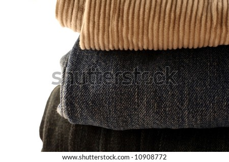 folded and stacked pants on a white background
